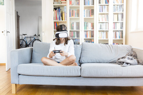 Girl sitting on the couch at home using Virtual Reality Glasses - LVF07518