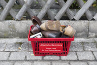 Germany, collection of donated old shoes in shopping basekt on pavement - KLRF00729