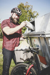 Portrait of cyclist recycling waste paper in paper bank - REAF00443