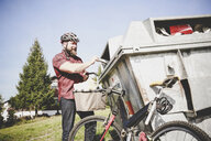 Cyclist recycling waste paper in paper bank - REAF00446