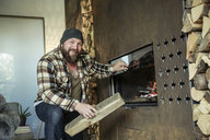 Portrait of bearded man lighting fireplace at home - REAF00455