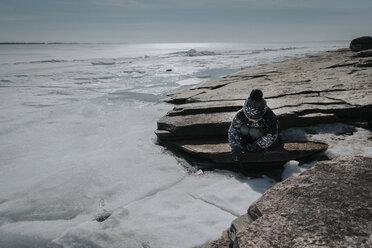 Boy sitting on rocks by frozen lake against sky - CAVF52631