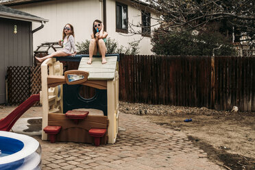 Sisters having popsicles while sitting on outdoor play equipment at backyard - CAVF52664