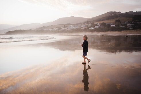 Side view of boy looking away while walking at beach against sky during sunset - CAVF52673