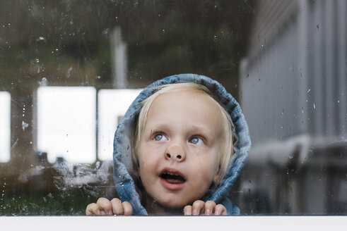 Close-up of girl looking through window seen through glass - CAVF52676