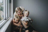 Happy mother with children sitting by window at home - CAVF52679