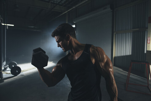 Male athlete lifting dumbbell while standing in gym - CAVF52682