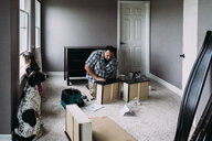 Father repairing drawers while daughter looking through window at home - CAVF52700