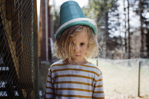 Portrait of girl with pot on head standing in yard - CAVF52706
