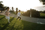 Mother running behind son on grassy field against sea during sunset - CAVF52727