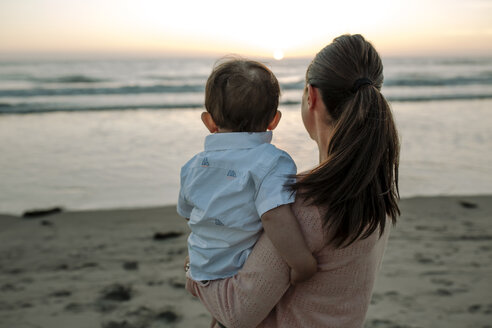 Side view of mother carrying son while standing at beach against sky during sunset - CAVF52730