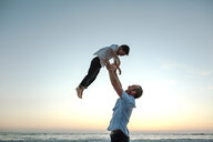 Happy father throwing son while standing at beach against sky during sunset - CAVF52736