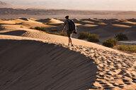 USA, Californien, Death Valley, Death Valley National Park, Mesquite Flat Sand Dunes, man walking on dune - FCF01524