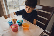 Boy making Easter eggs on table while sitting at home - CAVF52771