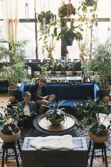 Gay men reading books while sitting amidst potted plants at home - CAVF52816