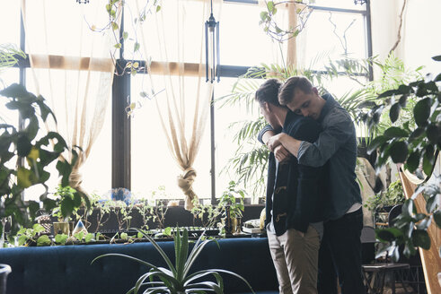 Gay man embracing boyfriend while standing against potted plants at home - CAVF52825