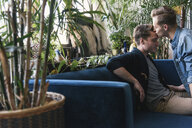 Gay man kissing on boyfriend's forehead against potted plants at home - CAVF52828