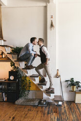 Full length of loving gay couple kissing on stairs against wall at home - CAVF52834