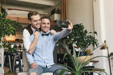 Cheerful gay couple taking selfie with smart phone at home - CAVF52849