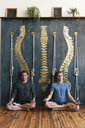Gay couple meditating while sitting against spine paintings at home - CAVF52852