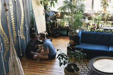 Side view of gay couple kissing while sitting on hardwood floor at loft apartment - CAVF52855