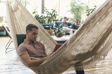 Gay man relaxing in hammock while boyfriend sitting on sofa against potted plants at home - CAVF52858