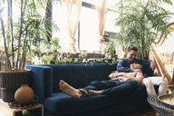 Loving Gay couple talking while relaxing on sofa against potted plants at home - CAVF52864