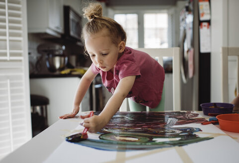 Girl painting on paper while standing by table at home - CAVF52867