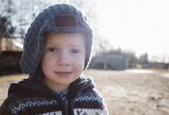 Close-up portrait of boy in warm clothing standing on field against clear sky - CAVF52870