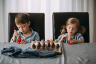 Siblings making Easter eggs on table at home - CAVF52891