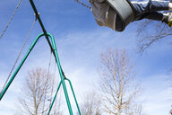 Low section of boy swinging on swing against sky at playground - CAVF52899