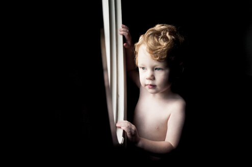 Shirtless baby boy looking through window while standing in darkroom at home - CAVF52953