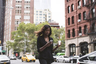 Businesswoman with coffee using smart phone while walking on city street - CAVF52971