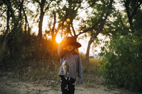 Girl wearing hat while holding fish in forest during sunset - CAVF53025