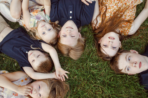 High angle view of siblings lying on grassy field - CAVF53034