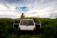 Rear view of woman photographing sunflowers on field while standing in car against cloudy sky - CAVF53045