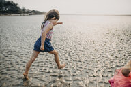 Side view of girl walking on sand at beach against sky - CAVF53051
