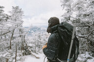Backpacker wearing warm clothing standing in forest during winter - CAVF53087