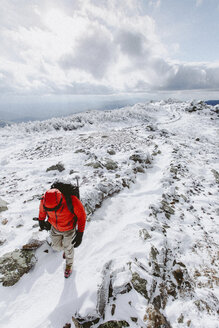 High angle view of backpacker wearing warm clothing walking on snow during winter - CAVF53090