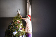 Low angle view of girl decorating Christmas tree at home - CAVF53096