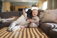 Portrait of cute baby boy playing with dog on couch in living room at home - CAVF53120