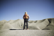 Rear view of male hiker standing at desert against clear blue sky - CAVF53141