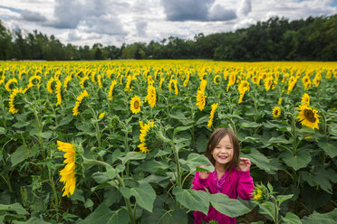 Portrait of cute happy girl standing at sunflower farm against cloudy sky - CAVF53150