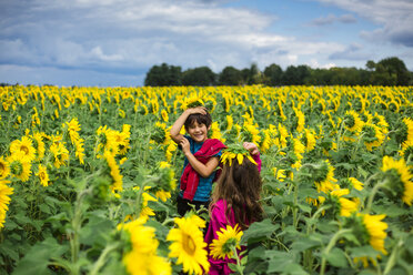Siblings playing with sunflowers while standing at farm against cloudy sky - CAVF53153