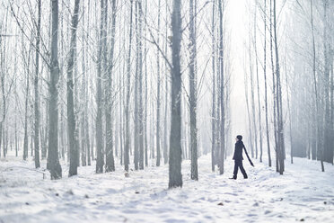 Full length of young man wearing black warm clothing while walking amidst trees at forest during foggy weather - CAVF53162