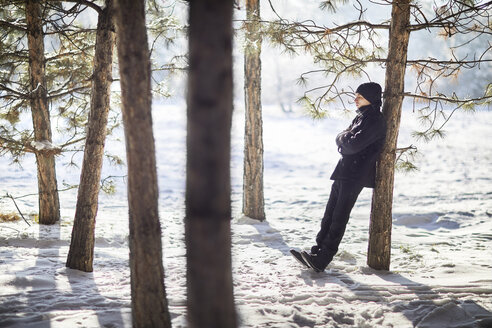 Full length of young man wearing black warm clothing while leaning on tree trunk at forest during winter - CAVF53165
