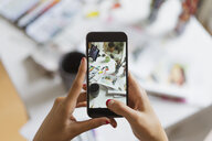 Illustrator's hands taking photo of work desk in atelier with smartphone, close-up - AFVF01933