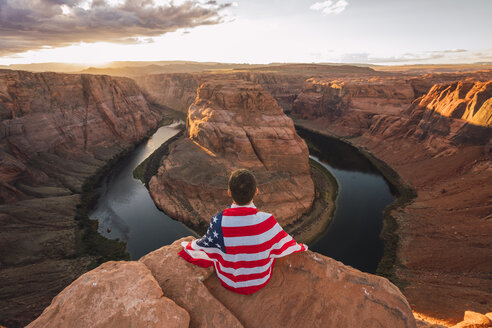 USA, Arizona, Colorado River, Horseshoe Bend, young man sitting on viewpoint with American flag - KKAF02844