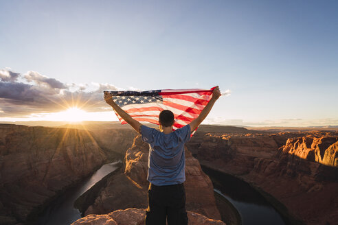 USA, Arizona, Colorado River, Horseshoe Bend, young man on viewpoint with American flag - KKAF02847