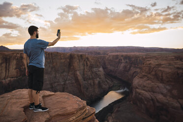 USA, Arizona, Colorado River, Horseshoe Bend, young man on viewpoint using smartphone, photographing - KKAF02853